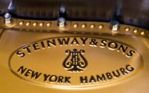 A Steinway piano plate with New York and Hamburg listed.