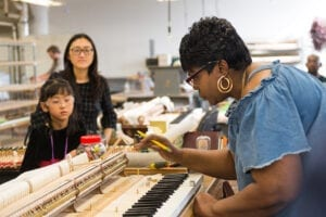 Photo of a Steinway craftswoman working on a keyboard.