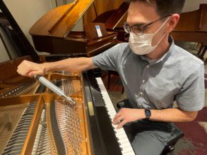 Photo of technician working on piano strings