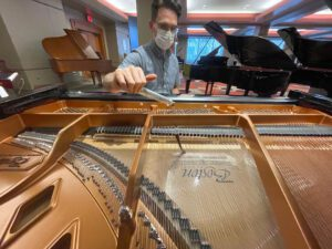 Photo of tuner looking at a piano's strings