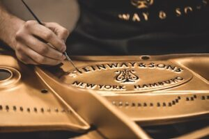 Photo of Steinway logo being painted in a piano interior
