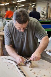 Steinway craftsman working on a soundboard.
