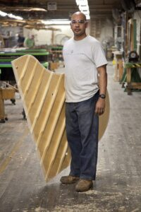 """The Steinway craftsman known as the """"bellyman"""" with a soundboard"""