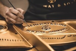 A Steinway craftsperson puts the final touches on the cast iron plate.