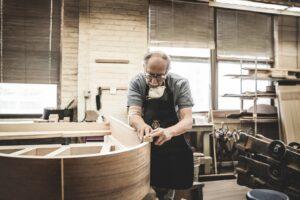 Steinway & Sons craftsman working on grand piano's rim